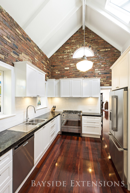 white kitchen with brick walls