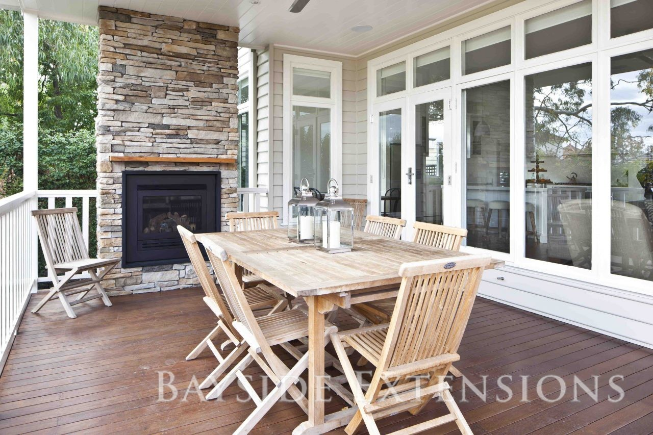 patio with wooden table and fireplace
